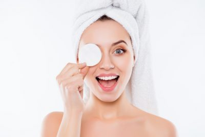 Portrait of foolish playful woman using sponge for application of lotion close one eye with cotton keeping open mouth with towel on head isolated on white background.